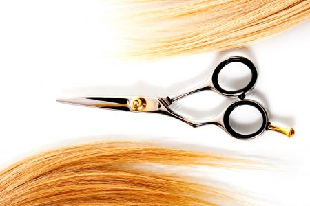 scissors and lock of hair isolated on white