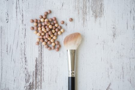 Blush beads and make-up brush, directly above shot.